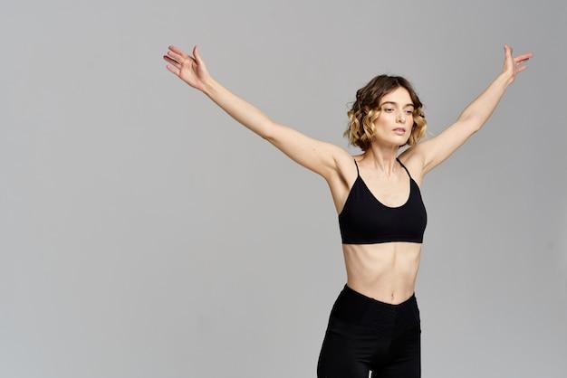 Slim jeune femme pratique le yoga et les exercices à la maison en studio