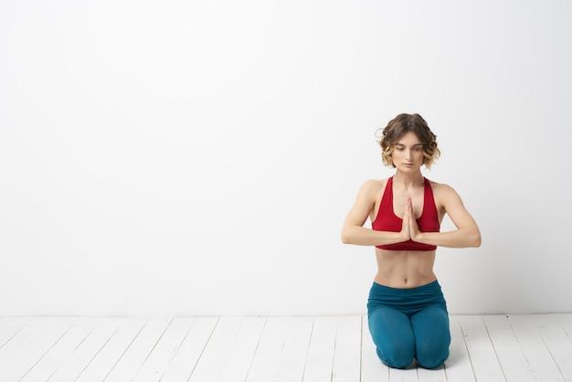 Slim jeune femme pratique le yoga et des exercices à la maison