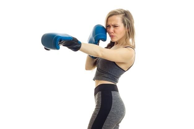 Slim jeune femme se tient sur le côté dans des gants de boxe est isolé sur un mur blanc