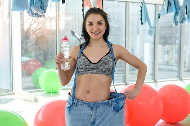 Slim jeune femme séduisante avec une bouteille d'eau et montre le résultat de la perte de poids au club de remise en forme ou à la salle de sport. mode de vie sain