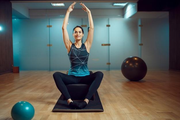 Slim woman in yoga pose sur la formation pilates sur tapis dans la salle de gym, flexibilité. workuot de remise en forme dans un club de sport.