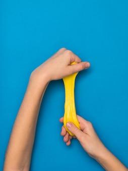 Slime jaune vif tendu dans les mains sur un fond bleu vif. jouet antistress. jouet pour le développement de la motricité de la main.