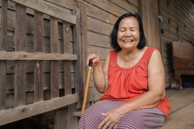 Slow-motion of thai femme âgée en col rond sans manches en riant dans la vieille maison en bois