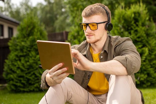 Smart bel étudiant masculin dans les écouteurs détient l'application d'apprentissage de la musique de test du pavé tactile, jeune homme implantation sur l'herbe dans le parc au repos travaillant sur une tablette numérique. étude à distance, concept d'applications de formation