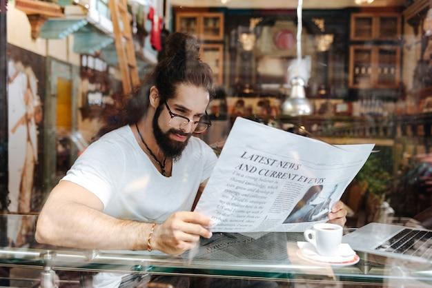 Smart bel homme holing un journal tout en lisant les nouvelles du matin