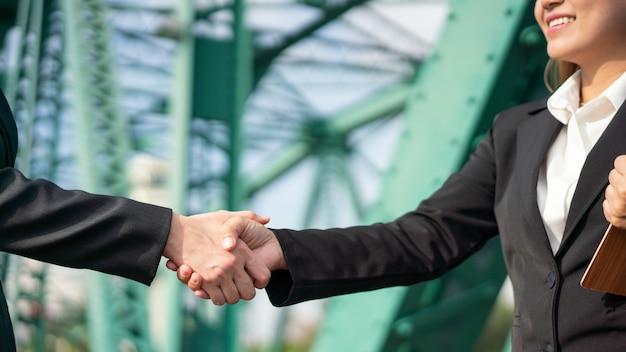 Smart business woman handshaking avec un sourire heureux dans une affaire réussie