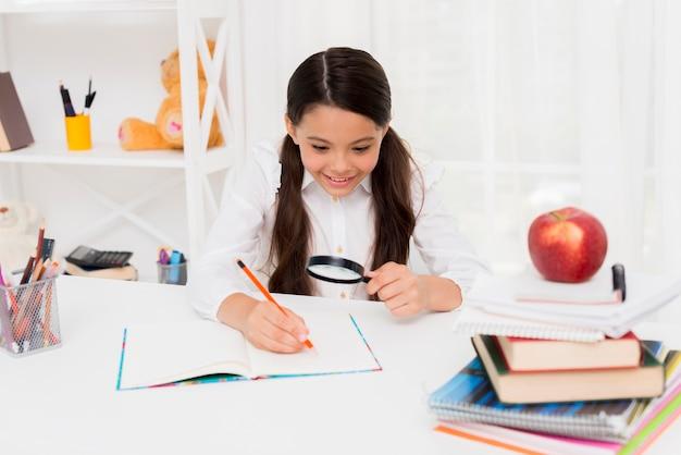 Smart écolière hispanique lisant à travers la loupe