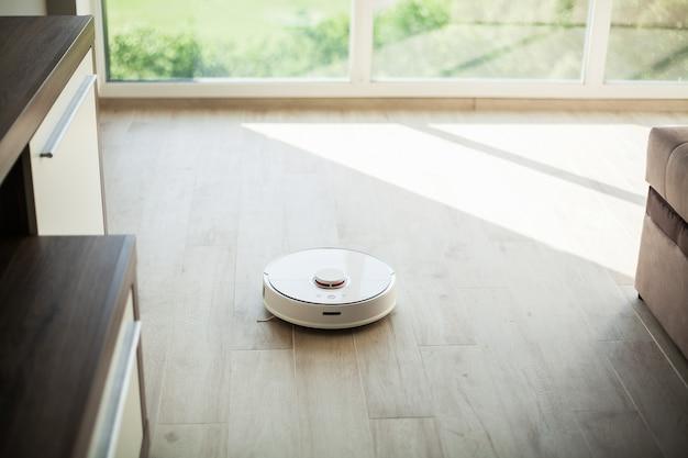 Smart house, robot aspirateur fonctionne sur un plancher de bois dans un salon