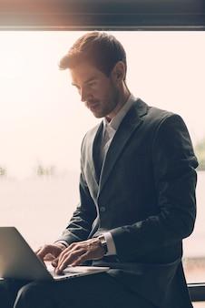 Smart jeune homme d'affaires en tapant sur un ordinateur portable