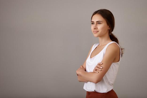 Smart mignonne belle jeune femme avec charmant sourire heureux posant dans une posture confiante avec les bras croisés sur sa poitrine, regardant devant elle vers un avenir meilleur et brillant, ayant une expression de rêve