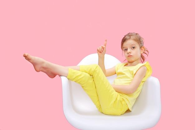 Smart petite fille pointant vers le haut sur rose