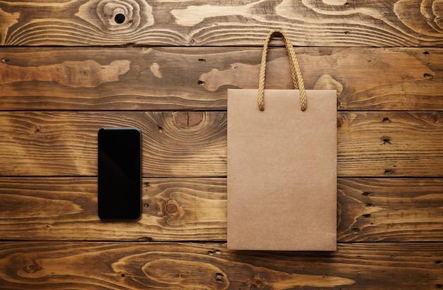 Smarthpone noir allongé à côté d'un sac en papier craft avec des poignées de ficelle marron clair sur une belle table en bois, tourné du haut
