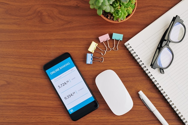 Smartphone avec application bancaire en ligne sur table