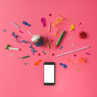 Smartphone avec des articles de fête colorés sur un mur rose. mise à plat.
