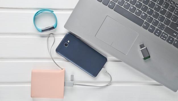 Smartphone, banque d'alimentation, bracelet intelligent, clé usb, ordinateur portable sur un bureau en bois blanc. vue de dessus. appareils et gadgets modernes.