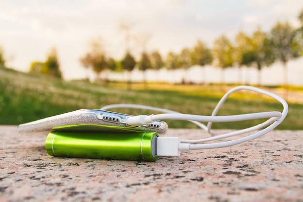 Smartphone et banque d'alimentation externe reposent sur la surface de granit dans le parc pendant le chargement