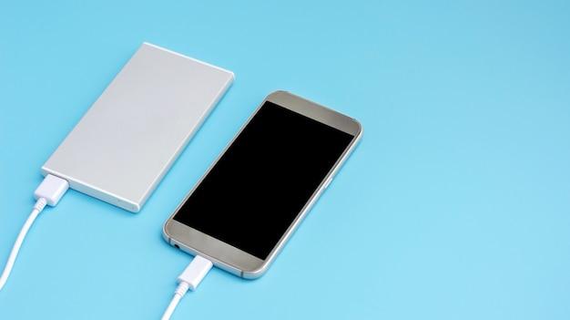 Smartphone et banque d'alimentation pour charger des appareils mobiles sur un fond bleu.