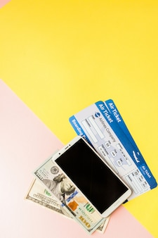 Smartphone, billet d'avion et dollars