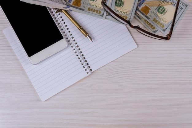Smartphone, billets de dollar en papier à côté d'un stylo et des lunettes