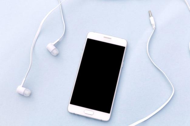 Smartphone blanc et un casque blanc sur fond bleu.