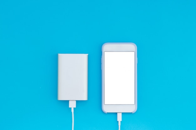Smartphone blanc et chargeur power bank sur fond bleu. vue de dessus de l'endroit pour le texte.