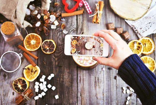Un smartphone blanc dans la main d'une femme prend la photo d'une tasse avec une boisson et des morceaux de guimauve