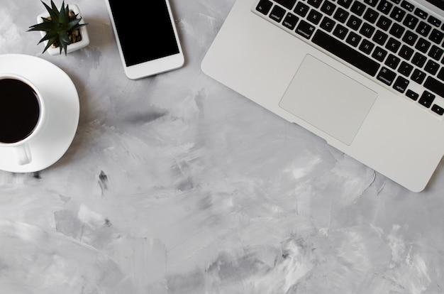 Smartphone blanc avec écran blanc noir sur le bureau avec ordinateur portable et tasse de café. maquette de téléphone.