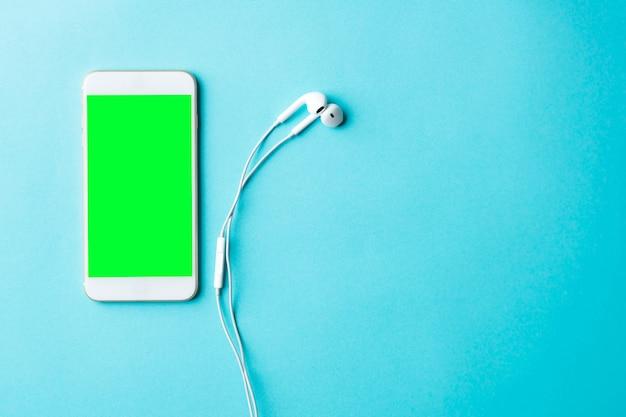 Smartphone blanc avec écran noir et écouteurs sur table en bois. vue de dessus avec espace copie, mise à plat.