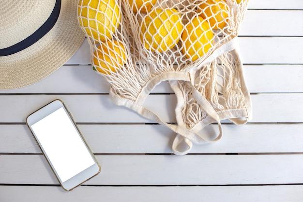 Un smartphone blanc se trouve sur une table en bois blanc, à côté se trouve un sac tricoté avec des citrons et une paille