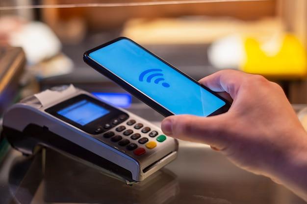 Smartphone en boutique utilisant la technologie nfc dans le contexte du terminal de paiement.