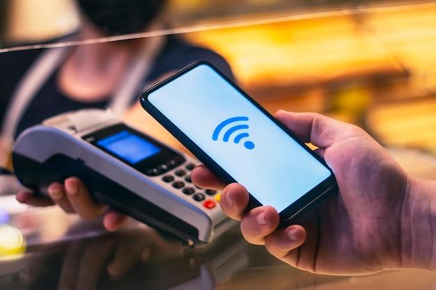 Smartphone en boutique utilisant la technologie nfc avec le terminal de paiement en arrière-plan