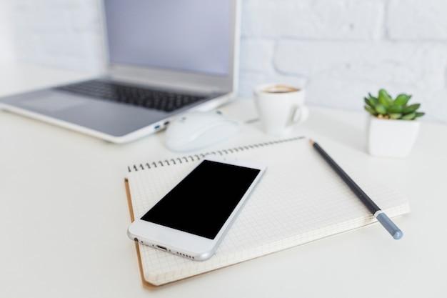 Smartphone, carnet et crayon en face de l'ordinateur portable sur un bureau blanc