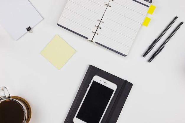 Smartphone avec carnet et tasse à café