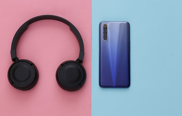 Smartphone avec casque stéréo noir sur pastel bleu rose