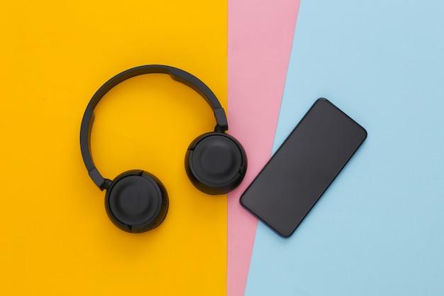 Smartphone avec casque stéréo noir sur table colorée