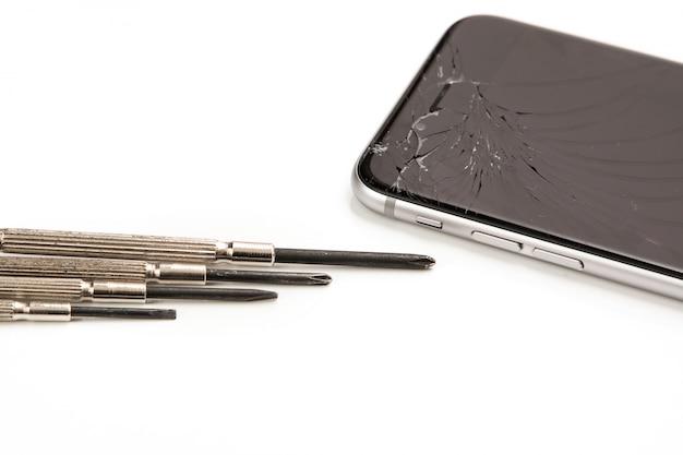 Smartphone cassé et petits tournevis pour réparation