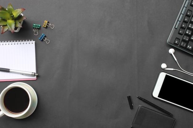 Smartphone, clavier, ordinateur portable, tasse à café, stylo et fournitures sont placés sur un bureau noir dans la