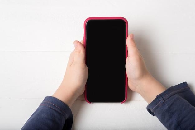 Smartphone dans les mains des enfants sur un fond clair