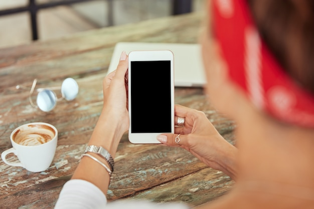 Smartphone dans les mains de la femme au café