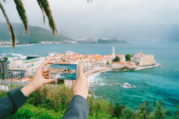 Smartphone dans les mains avec une photo contre la vieille ville du monténégro