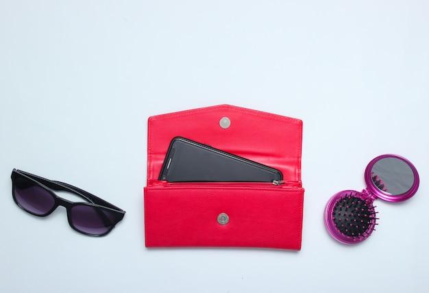 Smartphone dans un portefeuille en cuir rouge, lunettes de soleil, brosse à cheveux miroir sur blanc. vue de dessus