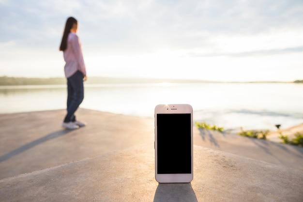 Smartphone devant une femme debout près du lac idyllique