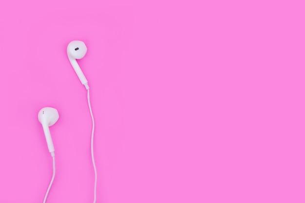 Smartphone avec des écouteurs sur rose avec espace de copie et un tracé de détourage. lay plat. vue de dessus.
