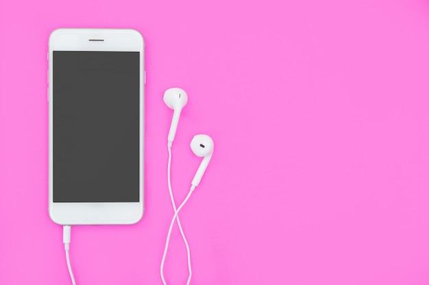 Smartphone avec écouteurs sur rose