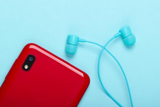 Smartphone avec écouteurs sous vide sur un bleu