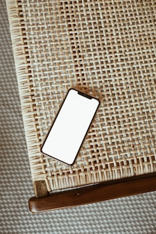 Smartphone à écran blanc sur chaise en rotin. mise à plat, vue de dessus