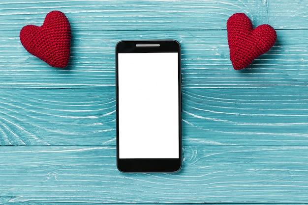 Smartphone avec écran blanc et coeur tricoté sur un beau fond en bois bleu. concept de la saint-valentin