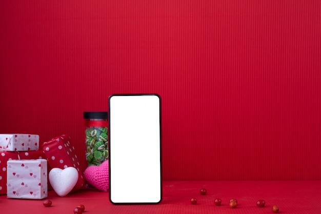 Smartphone avec écran blanc et coffrets cadeaux et coeurs. composition de la saint-valentin