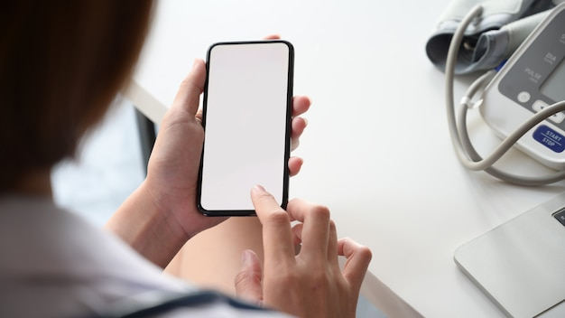 Smartphone avec écran blanc dans la main de la femme médecin