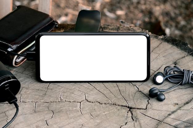 Smartphone avec écran blanc avec écouteurs, banque d'alimentation et portefeuille leath sur fond en bois.